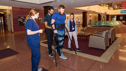 Patient using the ReWalk Exoskeleton with therapists assistance in the Atrium of Helen Hayes Hospital