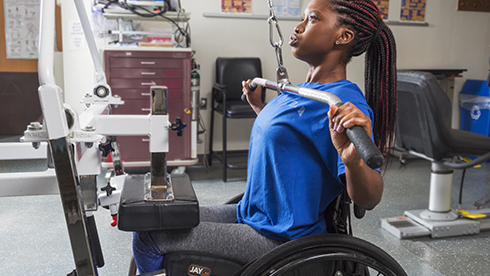 Patient in wheelchair using the pull-down weight machine in the Wellness Center at Helen Hayes Hospital