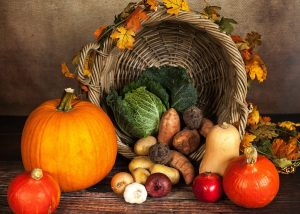 Basket set on its side with pumpkins, potatoes, lettuce, squash, onions, garlic, and turnips pouring from it