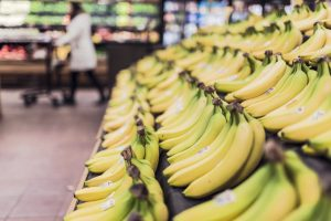 A side view of bunches of bananas lined up on a grocery shelf
