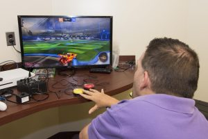 A patient in a power chair seen from behind, playing a racing game on the Xbox One using buddy button adaptive controllers