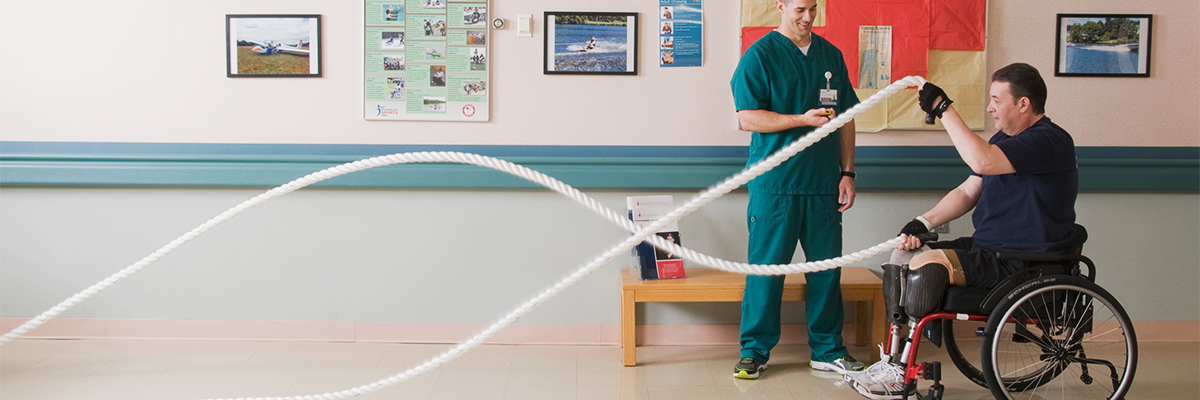 Amputee patient in a wheelchair using exercise ropes