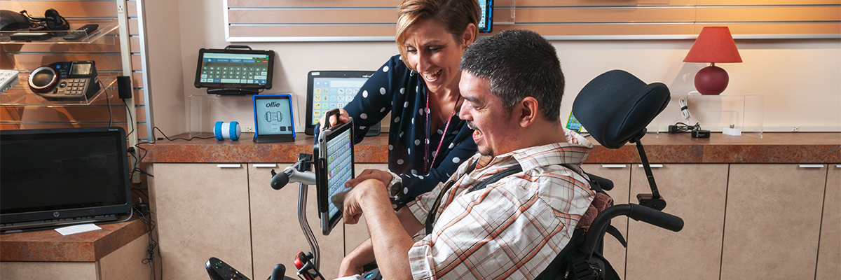 Man uses tablet to communicate with rehabilitation technology specialist