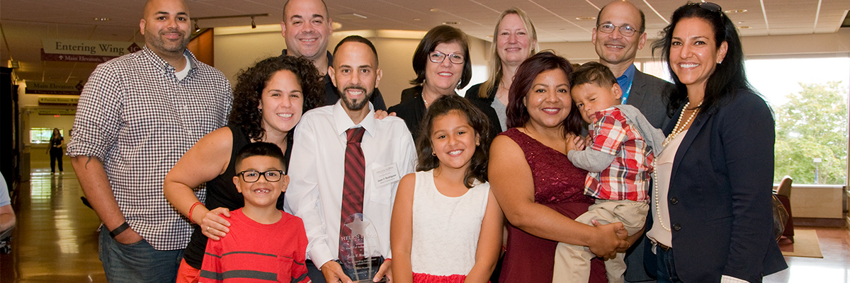 Former patient surrounded by family after receiving award