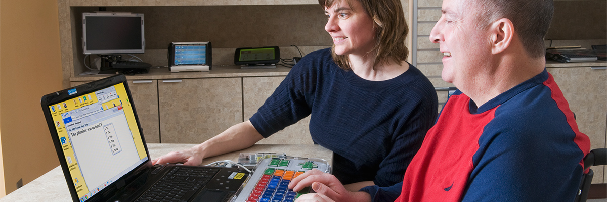 Therapist and patient working at a computer and practicing cognitive skills using adapted keyboard