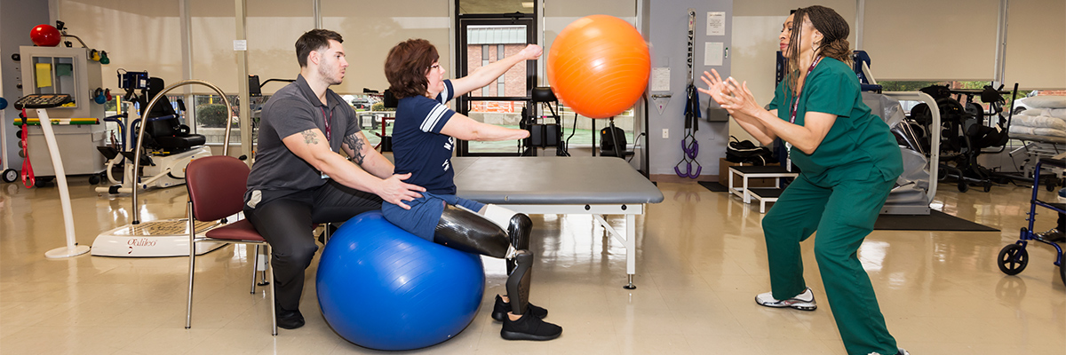 Female amputee sitting on a balance ball while throwing a ball for the physical therapist to catch
