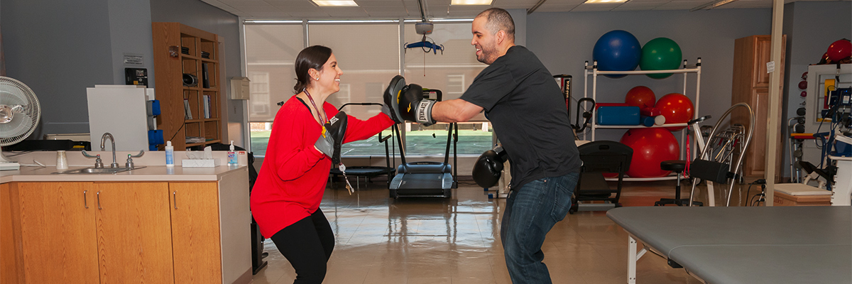 Therapist and patient boxing during outpatient neurological occupational therapy session
