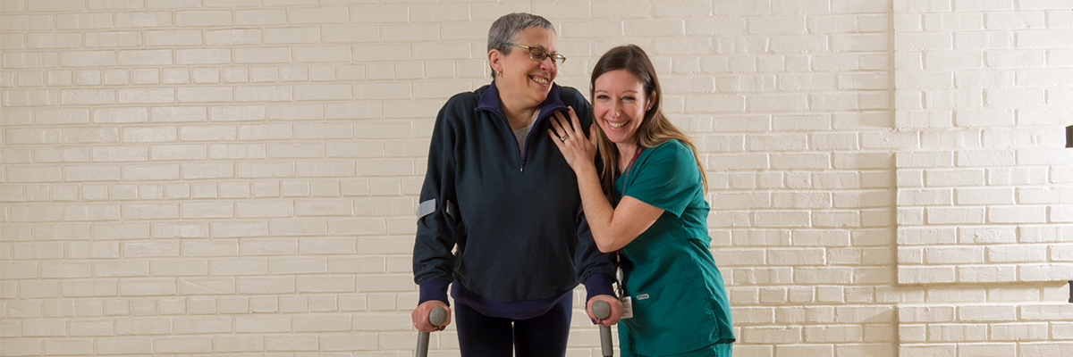 Patient using forearm crutches with therapist walking alongside her