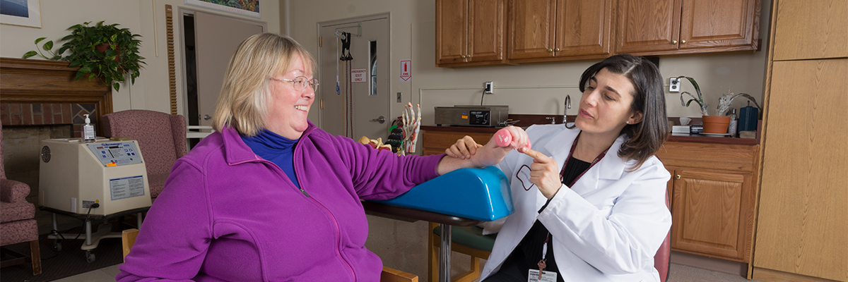 Hand therapist and patient seated and working on hand therapy on the patient's left hand