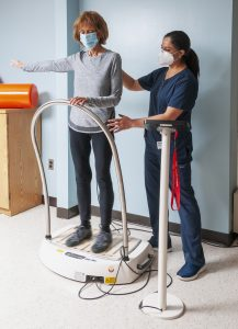 Physical Therapist is working with a patient using vibration therapy