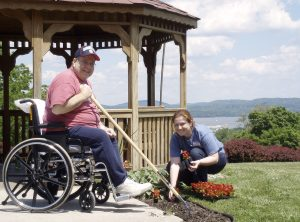 Man in wheelchair using adaptive gardening tool with long pole to reach flower garden bed. Women kneeling down opposite him. In front of a gazebo in Helen Hayes Hospital's MacArthur Park, overlooking the Hudson River.